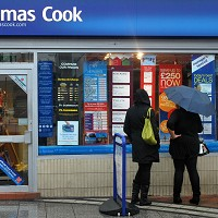 People shelter from the rain as they look at holidays displayed in the window of Thomas Cook