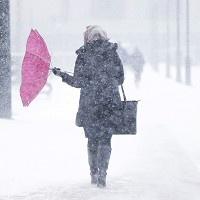 A woman's umbrella is blown around during a winter snowstorm in Philadelphia (AP)