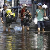 People carry their belongings along floods as they move to higher ground at one of Bangkok's districts