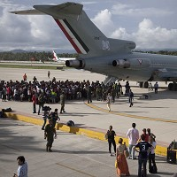 Hundreds of stranded tourists gather around a Mexican Air Force jet as they wait to be evacuated at the air base near Acapulco (AP)