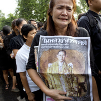 A Thai woman weeps as she holds on to a portrait of Thai King Bhumibol Adulyadej in a line to offer condolences for the king at Grand Palace in Bangkok