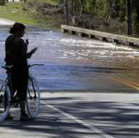 A woman watches flood waters rush over a bridge in North Carolina (AP)