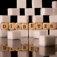 Close up on sugar cubes and dice spelling diabetes