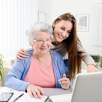 A senior woman is helped to use the internet