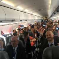 JetBlue flight 387 passengers hold up representations of Cuba's national flag, just before touching down at the airport in Santa Clara, Cuba.